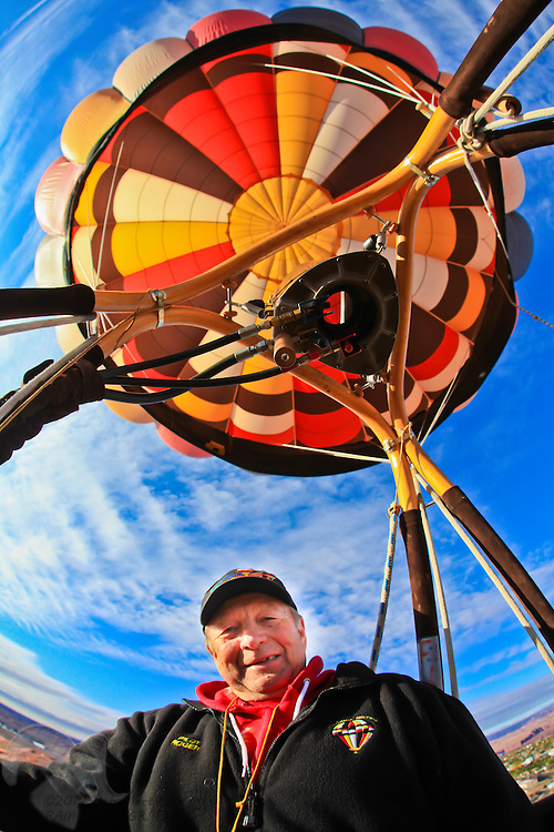 Hot-Air Balloon Pilot, Roger Hoppe, of Albuquerque, New Mexico flys above Page, Arizona while participating in the 2011 Balloon Regatta. Hoppe has over 40 years of experience flying balloons.