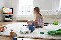 Girl (5-6) sitting on floor surrounded with toys watching television