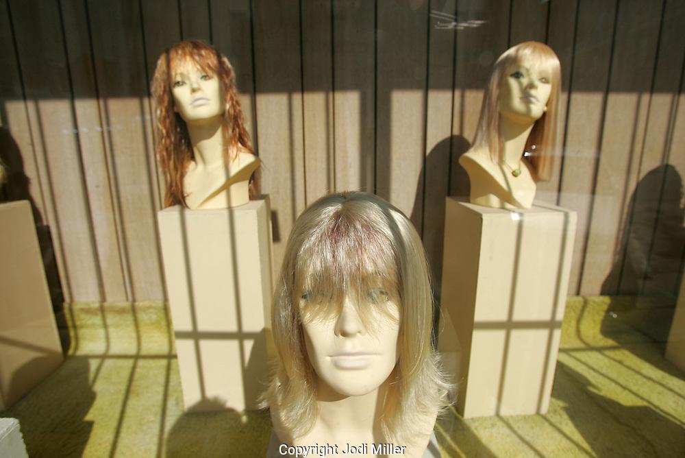 Women's wigs on mannequins in a store window.