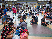 "03 JANUARY 2017 - BANGKOK, THAILAND: Travelers sit on the floor in Hua Lamphong Train Station in Bangkok. Travelers flocked to Bangkok's bus and train stations Tuesday, the last day of the long New Year's weekend in Thailand. The New Year holiday in Thailand is called the ""seven deadly days"" because of the number of fatal highway and traffic accidents. As of Monday Jan 2, 367 people died in highway accidents over the New Year holiday in Thailand, a 25.7% increase over the same period in 2016.          PHOTO BY JACK KURTZ"