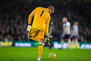 Kasper Schmeichel (GK) (Capt) (Leicester City) checks the bottom of his football boot before getting the ball back into play during the Premier League match between Brighton and Hove Albion and Leicester City at the American Express Community Stadium, Brighton and Hove, England on 23 November 2019.