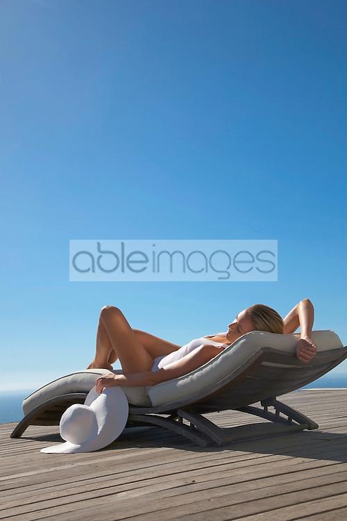Woman sunbathing on a sun lounger against blue sky