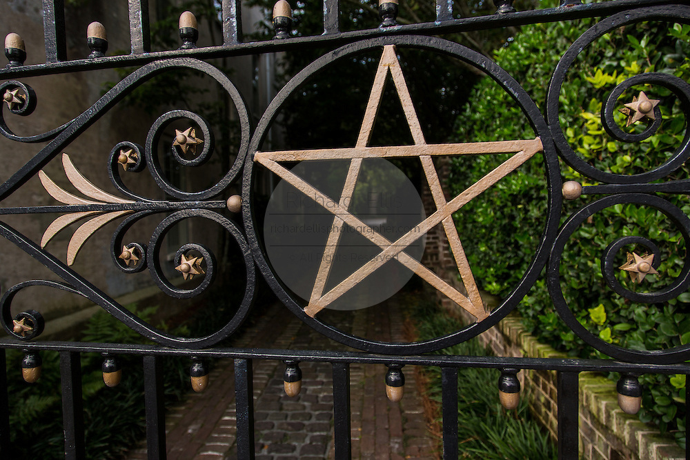A decorative iron gate at the entry to a quiet garden Charleston.