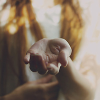 faceless portrait of a young girl in white holding her hand in front of her