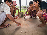 12 JUNE 2013 - YANGON, MYANMAR: Steverdores play a form of jacks while taking a break from unloading a rice barge along the Irrawaddy River in Yangon, Myanmar. Myanmar, formerly Burma, was to be the biggest rice producer and exporter in the world before World War II. But since the war, Myanmar's rice production has plummeted and now it is a rice importer.          PHOTO BY JACK KURTZ