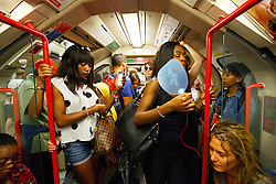 © Licensed to London News Pictures. 20/07/2016. London, UK. A woman uses a fan to stay cool whilst traveling on the tube in central London when temperatures hit 27C degrees across the capital on Wednesday, 20 July 2016. Photo credit: Tolga Akmen/LNP