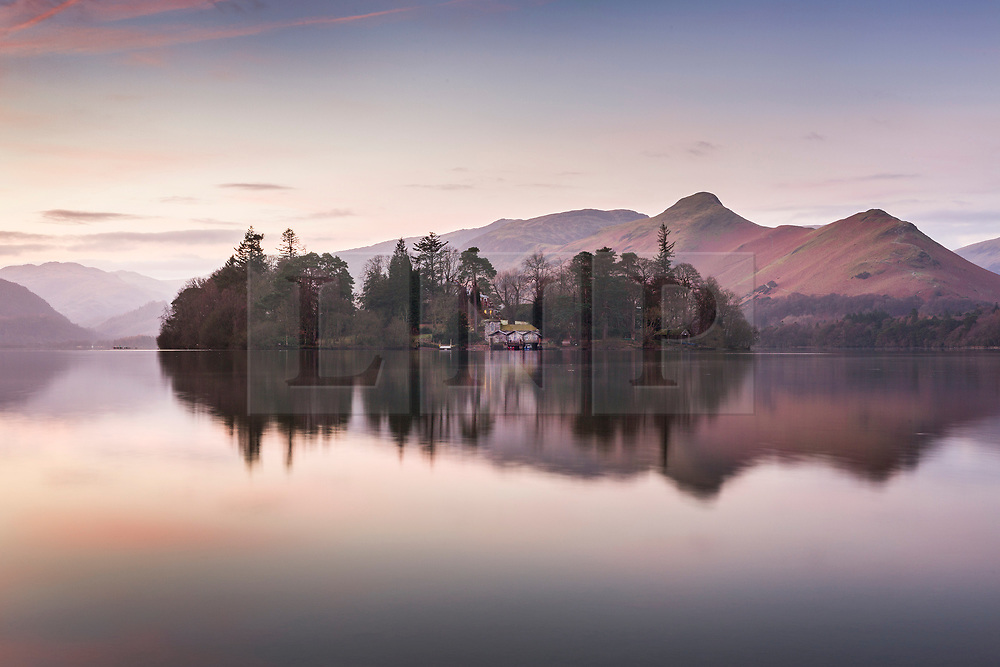 © Licensed to London News Pictures. 02/01/2019. Keswick UK. Derwent Isle & the surrounding mountains reflect into the calm surface of Derwent Water in Keswick at Dawn this morning in Cumbria. Photo credit: Andrew McCaren/LNP
