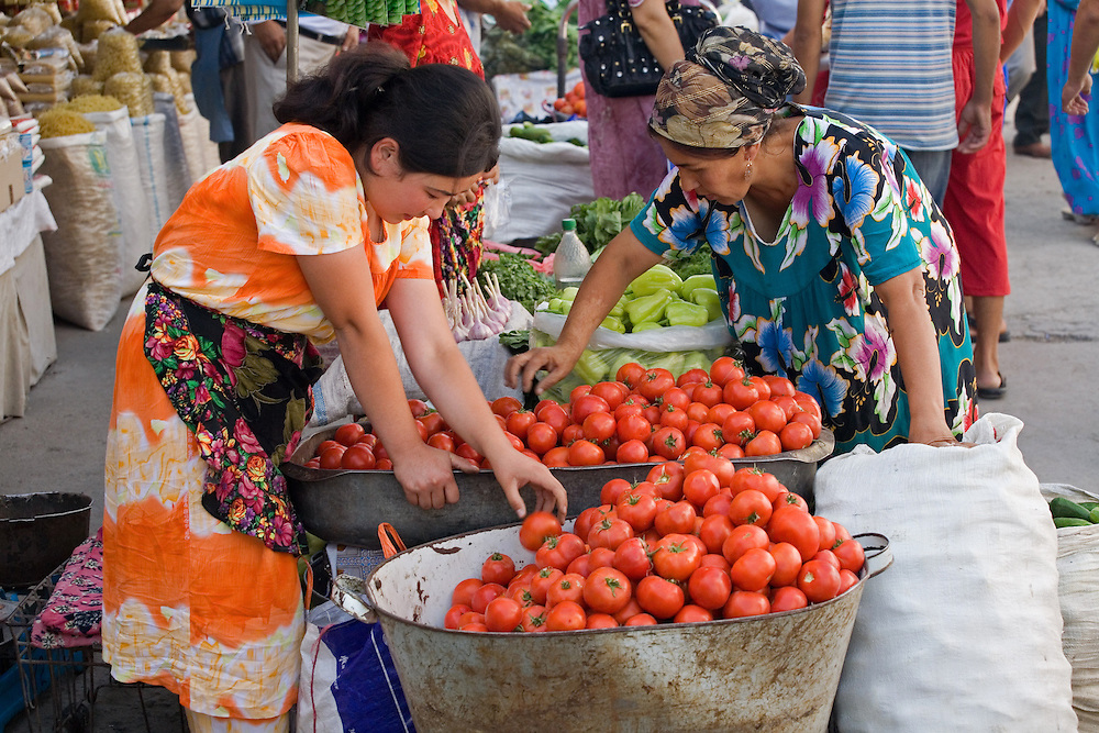 Women pick through tomatoes for sale in market, Khujand