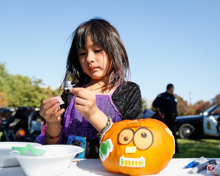 Vanessa Gonzalez, 6, of Milpitas decorates a pumpkin during the annual Sunnyhills Neighborhood Association's Sunnyhills Pre-Halloween Party at Albert Augustine Jr. Memorial Park in Milpitas, California, on October 26, 2013. (Stan Olszewski/SOSKIphoto)