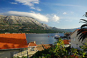 Elevated view over rooftops, looking North across the Peljeski Kanal, toward the Peljesac Peninsular (Croatian mainland), with large cloud formation on mountain. Island of Korcula, Croatia