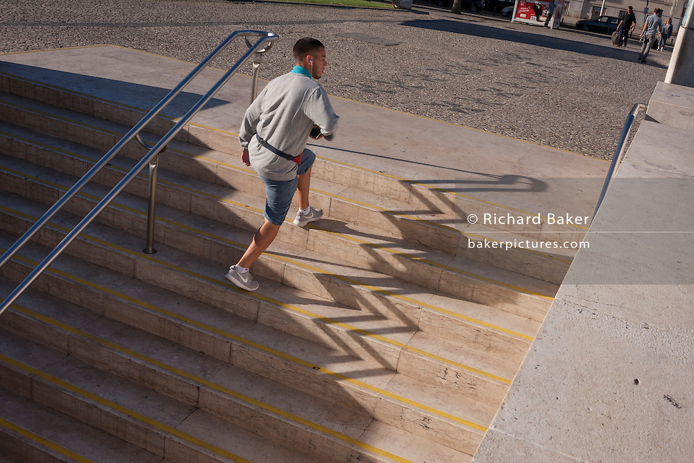 A young man leaps past the zigzag shadows of steps at Alameda metro station, Lisbon, Portugal.