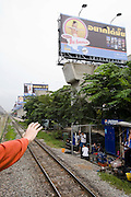 Eastern & Oriental Express. The train slowly leaves Bangkok, passing klongs, slums and suburbs. Concrete stilts for an elevated track planned for the future, lined by giant ads.
