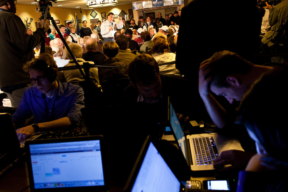 Reporters work on their computers as Republican presidential candidate Mitt Romney meets with voters at the Stoney Creek Inn on Saturday, December 31, 2011 in Sioux City, IA.