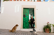 An elderly woman leaves her home on the island of Crete in Greece, as she prepares to walk her two dogs. . Commissioned by PR Media Co.
