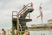 "Children swimming and diving in the lido by the beach in St. Malo. Saint-Malo is a walled port city in Brittany in northwestern France on the English Channel. Traditionally with an independent streak, Saint-Malo was in the past notorious for privateering (the ""cité corsaire""). Today the city is a major tourist destination, with many ancient, attractive buildings."