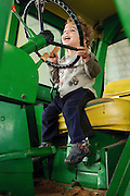 Toddler plays on a tractor