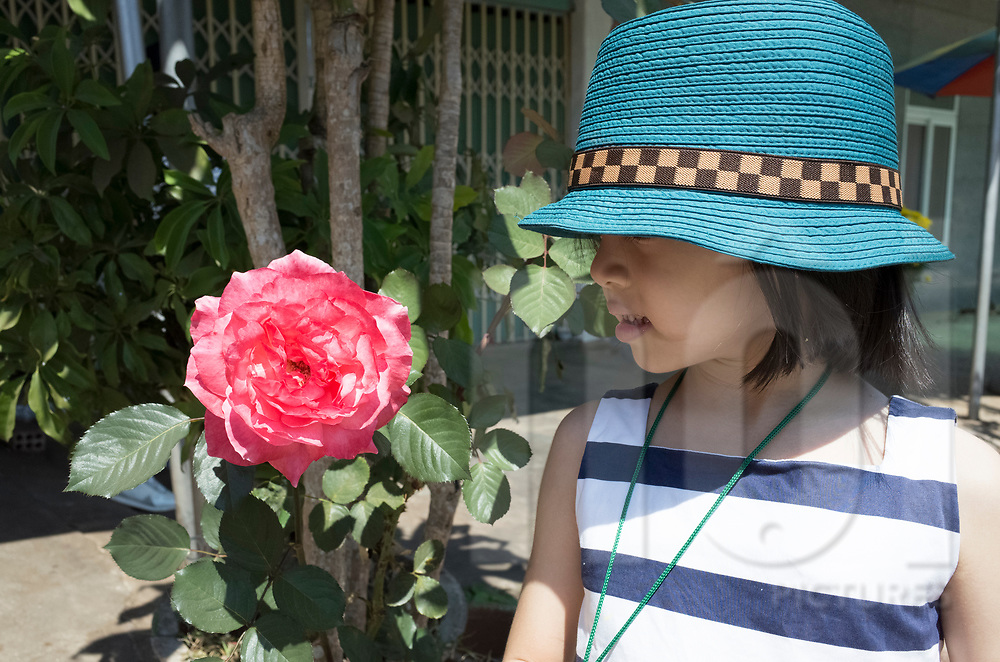 A young Vietnamese girl poses nearby a rose, Vietnam, Southeast Asia