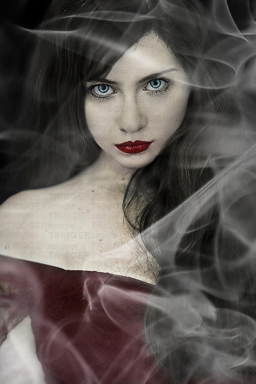 A girl wearing red with smoke swirling around her.