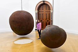 """© Licensed to London News Pictures. 17/09/2019. LONDON, UK. A visitor views """"Body"""", 1991/93, and """"Fruit"""", 1991/93, both by Antony Gormley. Preview of a new exhibition by Antony Gormley at the Royal Academy of Arts.  The show bring together existing and specially conceived new works from drawing to sculptures to experimental environments to be displayed in all 13 rooms of the RA's Main Galleries 21 September to 3 December 2019.  Photo credit: Stephen Chung/LNP"""