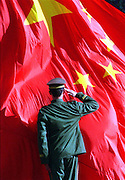 A Chinese soldier salutes a flag.