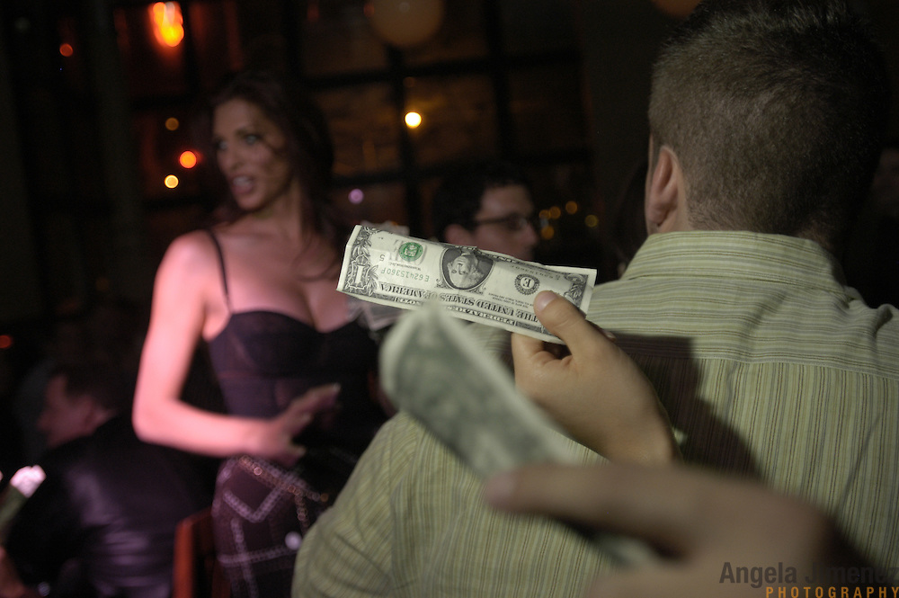 DATE: 10/23/04<br />DESK: METRO<br />SLUG: CAYNE<br /><br />Audience members offer up tips to performer Candis Cayne at the end of her weely performance of The Candis Cayne Show at The Tomato Restaurant on 6th Avenue and 21st Street in Manhattan.  <br /><br />photo by Angela Jimenez for The New York Times<br />photographer contact 917-586-0916