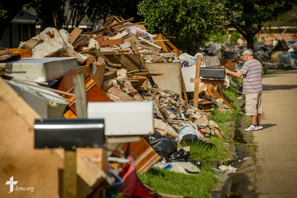 A homeowner collects his mail amongst a street full of flood-damaged debris in a neighborhood on Tuesday, Sept. 13, 2016, in Baton Rouge, La. LCMS Communications/Erik M. Lunsford