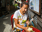 30 JULY 2016 - BANGKOK, THAILAND: A woman juliennes papaya to make Som Tam (papaya salad) in the Pom Mahakan Fort slum. Residents of the slum have been told they must leave the fort and that their community will be torn down. The community is known for fireworks, fighting cocks and bird cages. Mahakan Fort was built in 1783 during the reign of Siamese King Rama I. It was one of 14 fortresses designed to protect Bangkok from foreign invaders. Only of two are remaining, the others have been torn down. A community developed in the fort when people started building houses and moving into it during the reign of King Rama V (1868-1910). The land was expropriated by Bangkok city government in 1992, but the people living in the fort refused to move. In 2004 courts ruled against the residents and said the city could take the land. Eviction notices have been posted in the community and people given until April 30 to leave, but most residents have refused to move. Residents think Bangkok city officials will start evictions around August 15, but there has not been any official word from the city.      PHOTO BY JACK KURTZ