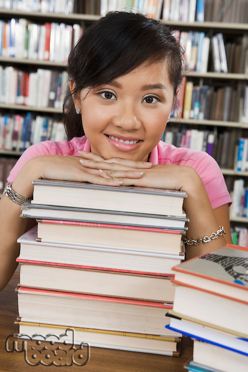 Student with a Stack of Books in Library