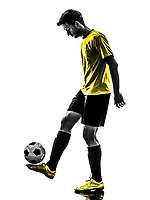 one Brazilian soccer football player young man juggling in silhouette studio on white background