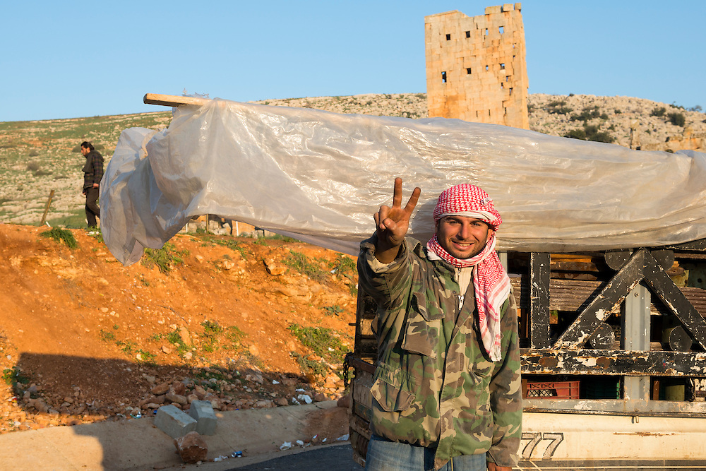 A Syrian man stands on the Syrian side of the Bab al-Hawa border crossing between Turkey and Syria, flashing a V-sign. Old ruins -- Byzantine-era? -- are in the background.