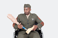 Sad US military officer in wheelchair holding prosthesis foot over gray background