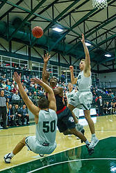 BLOOMINGTON, IL - November 12: Karson Hayes tosses up a shot as he runs into Charlie Bair and Luke Yoder during a college basketball game between the IWU Titans  and the Blackburn Beavers on November 12 2019 at Shirk Center in Bloomington, IL. (Photo by Alan Look)