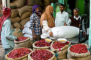 Businessmen and porters at stall selling red chillies at Khari Baoli spice and dried foods market, Old Delhi, India
