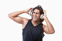 Young muscular man listening music through headphones over white background