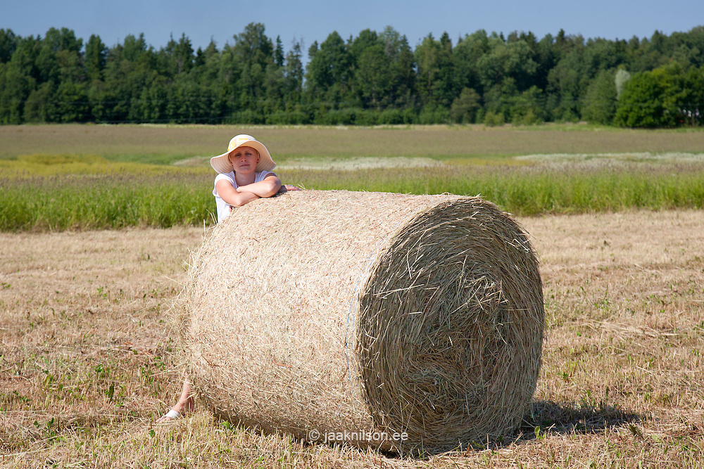 Young Woman in a Field, Leaning Against a Bale of Hay
