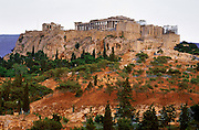 The Erechtheion (left) and Parthenon (right) sit prominently on the Acropolis in Athens, Greece, Europe. The Parthenon was first built from 447-438 BC, using Pentelic marble plus a wooden roof. The Parthenon is the largest Doric-column temple ever completed in Greece. It was designed as a treasury for tribute money moved from Delos Island and was dedicated to the worship of Athena. A huge, 12-meter tall statue of Athena Polias was placed in 432 BC. The Erechtheion, built entirely of marble in 421-406 BC, is the most sacred sanctuary on the Acropolis. The Acropolis of Athens and its monuments were honored as a UNESCO World Heritage Site in 1987.