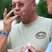 """June 9, 2012 - Vernon, NJ : Alex MacNeil licks his fingers as he eats barbecue during the 3rd annual 'Rock, Ribs & Ridges"""" music and food festival in Vernon, NJ on Saturday. CREDIT: Karsten Moran for The New York Times"""