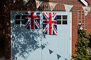 As the Coronavirus lockdown continues over the May Bank Holiday, the nation commemorates the 75th anniversary of VE Day (Victory in Europe Day, the day that Germany officially surrendered in 1945) and in Dulwich, neighbours and residents emerge from their homes to party while still observing social distancing rules. Union Jack flags hang from a garage door, on 8th May 2020, in London, England.