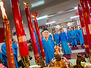 "09 FEBRUARY 2014 - HAT YAI, SONGKHLA, THAILAND:  Men light candles in the Chao Mae Tubtim Shrine (Ruby Goddess Shrine) on 108 Hainanese Ancestors Memorial Day in Hat Yai, Songkhla, Thailand. Hainanese communities around the world celebrate ""108 Hainanese Ancestors Memorial Day."" The day honors the time when 109 Hainanese villagers fleeing life in Hainan (an island off of the southwest coast of China, near Vietnam) washed up in what is now Vietnam and were killed by Vietnamese authorities because authorities thought they were pirates. The Vietnamese built a temple on the site and named it ""Zhao Yin Ying Lie."" Many Vietnamese fisherman credit prayers at the temple to saving their lives during violent storms and now ""108 Hainanese Ancestors Memorial Day"" is celebrated in Hainanese communities around the world. Hat Yai, the economic center of southern Thailand has a large Hainanese population.   PHOTO BY JACK KURTZ"