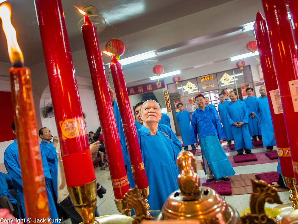 """09 FEBRUARY 2014 - HAT YAI, SONGKHLA, THAILAND:  Men light candles in the Chao Mae Tubtim Shrine (Ruby Goddess Shrine) on 108 Hainanese Ancestors Memorial Day in Hat Yai, Songkhla, Thailand. Hainanese communities around the world celebrate """"108 Hainanese Ancestors Memorial Day."""" The day honors the time when 109 Hainanese villagers fleeing life in Hainan (an island off of the southwest coast of China, near Vietnam) washed up in what is now Vietnam and were killed by Vietnamese authorities because authorities thought they were pirates. The Vietnamese built a temple on the site and named it """"Zhao Yin Ying Lie."""" Many Vietnamese fisherman credit prayers at the temple to saving their lives during violent storms and now """"108 Hainanese Ancestors Memorial Day"""" is celebrated in Hainanese communities around the world. Hat Yai, the economic center of southern Thailand has a large Hainanese population.   PHOTO BY JACK KURTZ"""