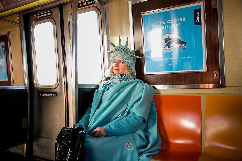 "QUEENS, NY - FEBRUARY 6, 2017: Lindley Hanlon rides the A train leaving John F Kennedy International Airport, where she dressed as the Statue of Liberty to welcome people entering through Terminal 4 in Queens, New York. While at the airport, law enforcement approached Hanlon and made her put away a sign that read ""Liberty and Justice for All."" Hanlon made her costume from Bed Bath and Beyond curtains and purchased the crown from a Halloween store in the East Village. ""I think it's more important than ever,"" she said about the Statue of Liberty. ""Because I think our liberties are threatened."" CREDIT: Sam Hodgson for The New York Times"
