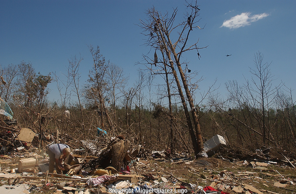Rainsville, Alabama: Shane Spillmen, from Fort Payne, helps a neighbor sift through a valley of debris in this rural northeastern Alabama town. A government helicopter surveys the damage overhead.  At least 32 people are confirmed dead in Rainsville and surrounding Dekalb County. (PHOTO: MIGUEL JUAREZ LUGO)