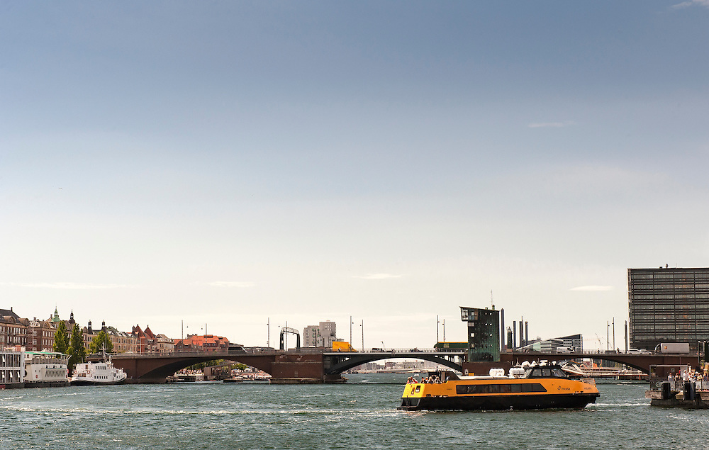 A view of Copenhagen Harbour and a yellow harbour water taxi. Langebro can be seen in the background
