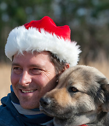 Portrait of a man wearing a Santa Claus hat and his dog