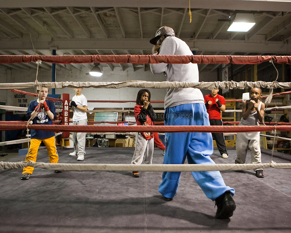 A group of young boxers practice the fundamentals of footwork with Alex Guerrero.