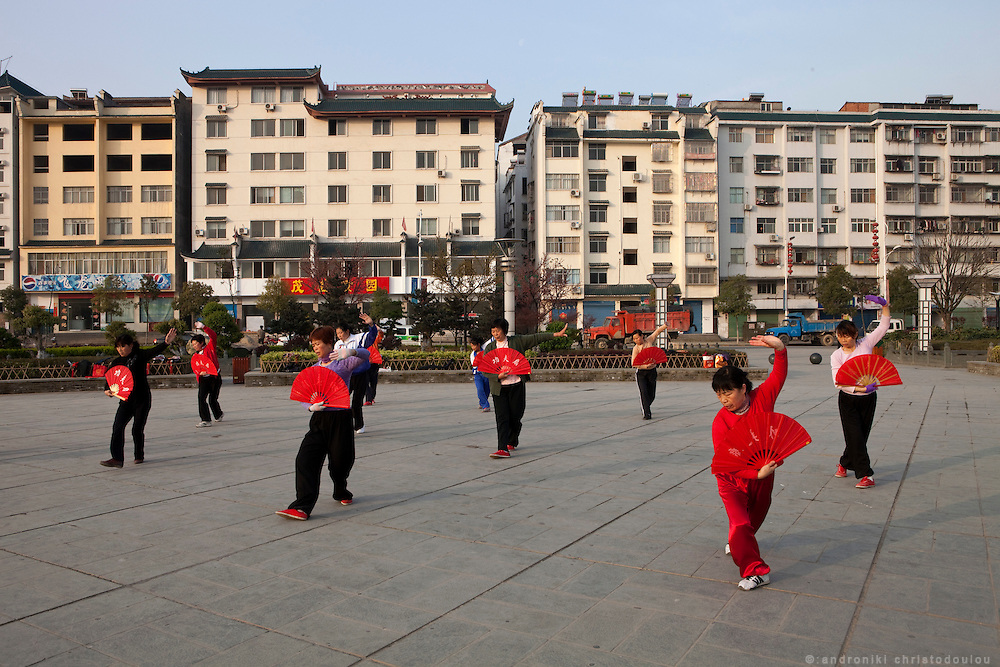 Asia, China, Hubei province.  Morning Tai Chi fan trainning at the main square outside the museum of the Wudnagsan city thaty lays on the feet of Wudang moutain (Wudang-san), a World Heritage mountain with many Taoist monasteries.