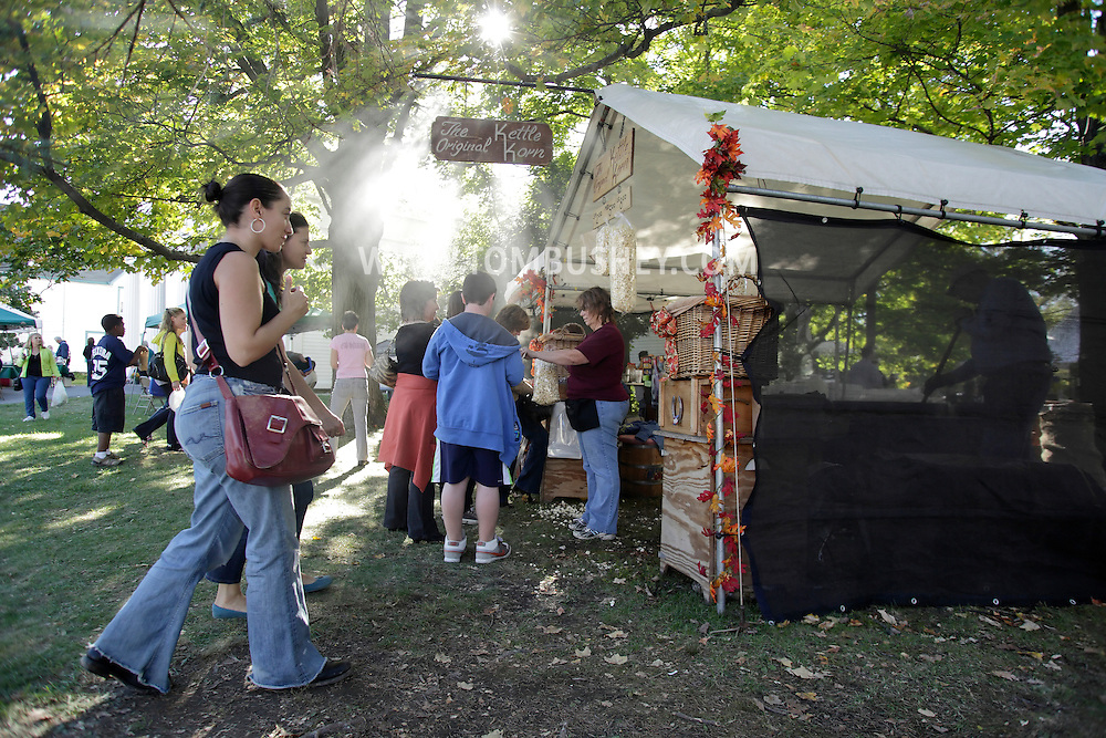Sugar Loaf, New York - A woman, at center, sells freshly-made Kettle Korn popcorn to people during the Sugar Loaf Fall Festival on Oct. 10, 2010. ©Tom Bushey / The Image Works