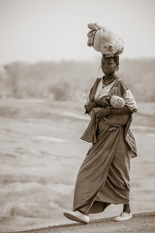 Portrait of a young Burkinabe mother carrying her baby and her goods on a long dusty trek to the market in the Sahel of northern Burkina Faso