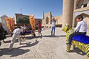 Uzbekistan, Khiva. Kultlimurodinok Medressa. Souvenir photographer with tiger for tourists.