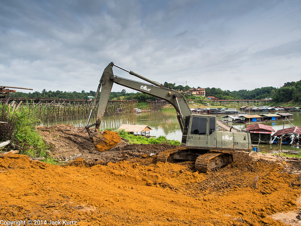 16 SEPTEMBER 2014 - SANGKHLA BURI, KANCHANABURI, THAILAND: Heavy equipment from the Royal Thai Army improves the approaches to the Mon Bridge. The 2800 foot long (850 meters) Saphan Mon (Mon Bridge) spans the Song Kalia River. It is reportedly second longest wooden bridge in the world. The bridge was severely damaged during heavy rainfall in July 2013 when its 230 foot middle section  (70 meters) collapsed during flooding. Officially known as Uttamanusorn Bridge, the bridge has been used by people in Sangkhla Buri (also known as Sangkhlaburi) for 20 years. The bridge was was conceived by Luang Pho Uttama, the late abbot of of Wat Wang Wiwekaram, and was built by hand by Mon refugees from Myanmar (then Burma). The wooden bridge is one of the leading tourist attractions in Kanchanaburi province. The loss of the bridge has hurt the economy of the Mon community opposite Sangkhla Buri. The repair has taken far longer than expected. Thai Prime Minister General Prayuth Chan-ocha ordered an engineer unit of the Royal Thai Army to help the local Mon population repair the bridge. Local people said they hope the bridge is repaired by the end November, which is when the tourist season starts.    PHOTO BY JACK KURTZ